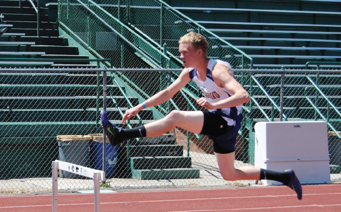 photo by Garrett Miller West Grand senior Josh O'Hotto keeps a steady pace in the hurdles to earn third.