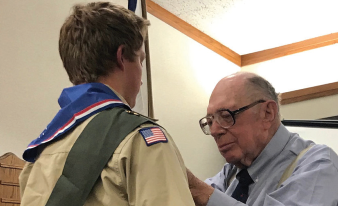 At the Eagle Scout ceremonyAt the Eagle Scout ceremony, Grandpa Noel Burns places Camden's Eagle, Grandpa Noel Burns places Camden's Eagle Scout neckerchief and slide.Scout neckerchief and slide.